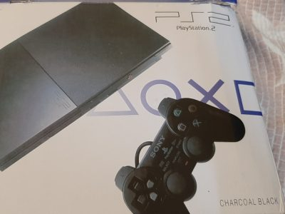 PS2 Slim with 4 cd and 2 controllers and a camera